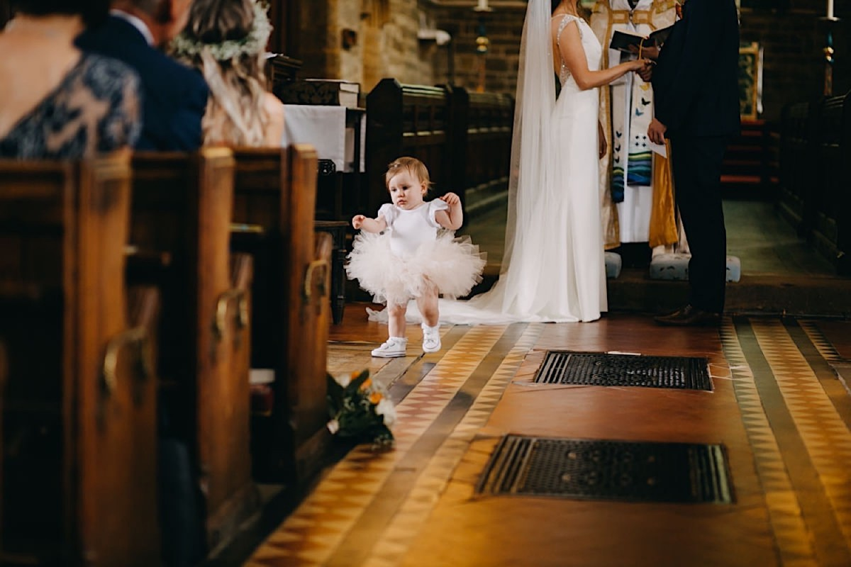 a little girl is walking down the isle while the bride and the groom are making their wedding vows documentary wedding photographer Nottingham