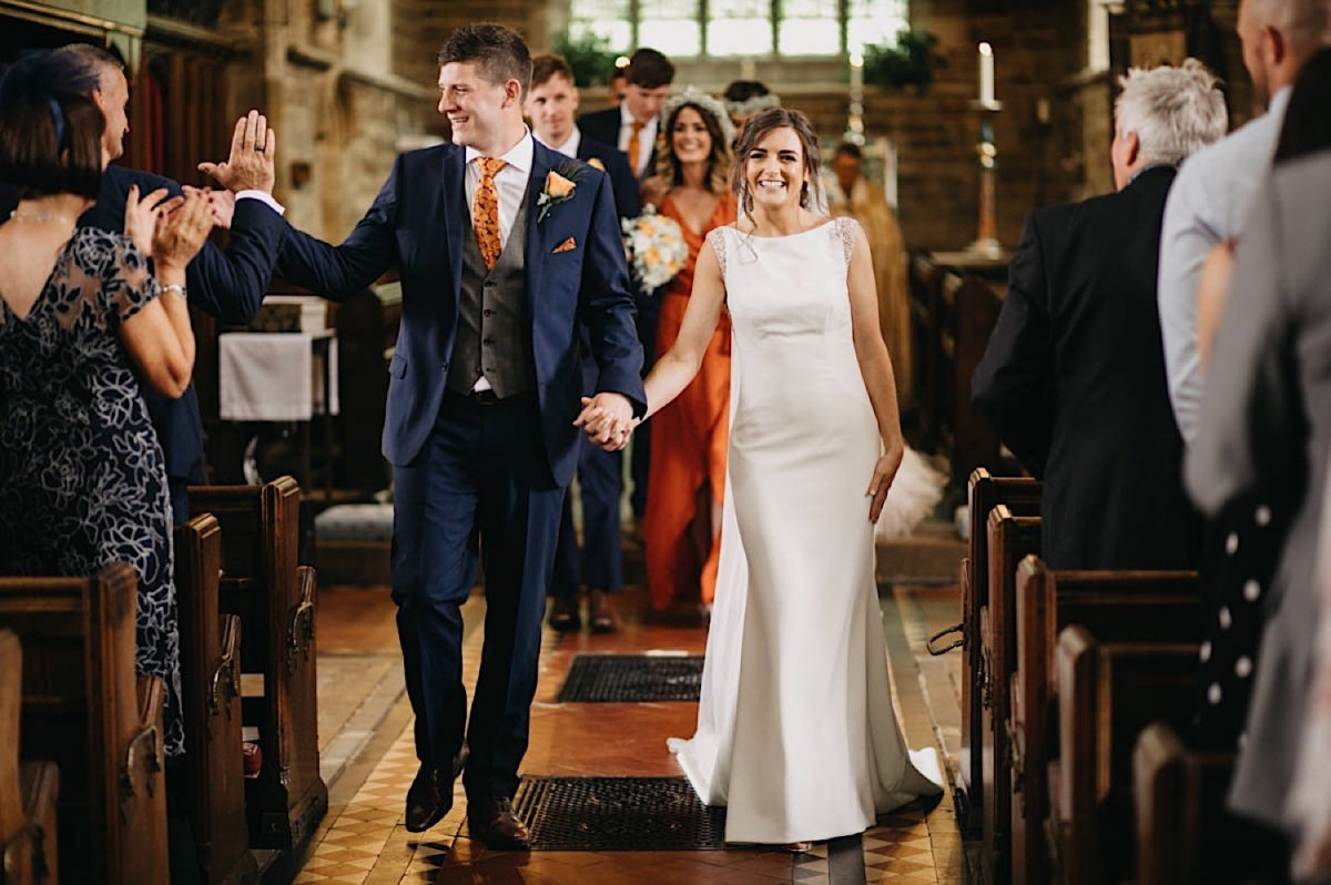 the bride and the groom walking the church's isle after the wedding ceremony with a joy documentary wedding photographer Nottingham