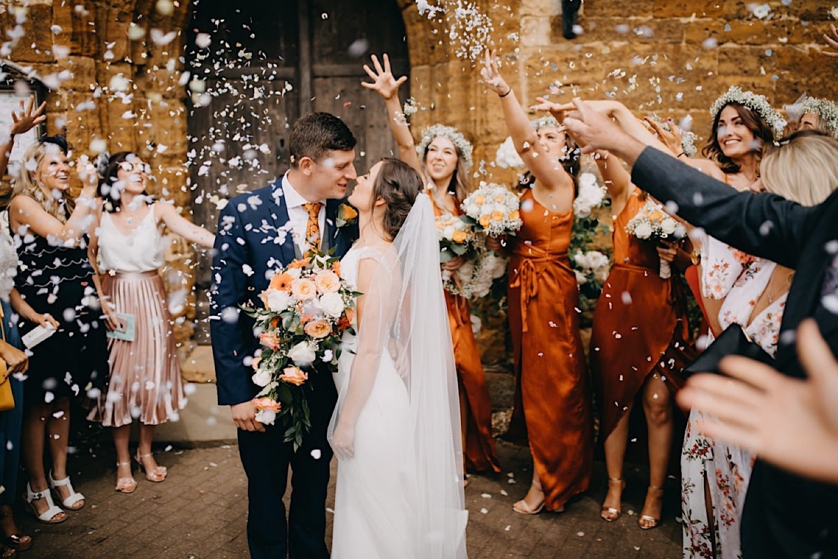 the groom and the bride are standing and kissing during wedding confetti documentary wedding photographer Nottingham