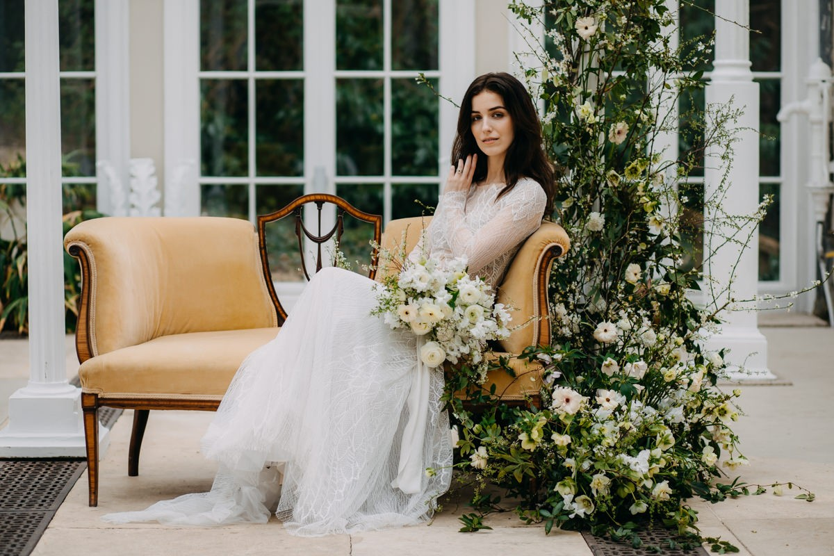 Tha-bride-sitting-on-the-chair-holding-wedding-bouqet-whith-flower-arrangement-aand-at-came-house