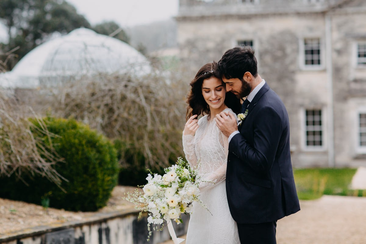 couple-cuddling-relexed-and-smiling-posing-in-front-of-came-house-romantic-wedding-portrait-