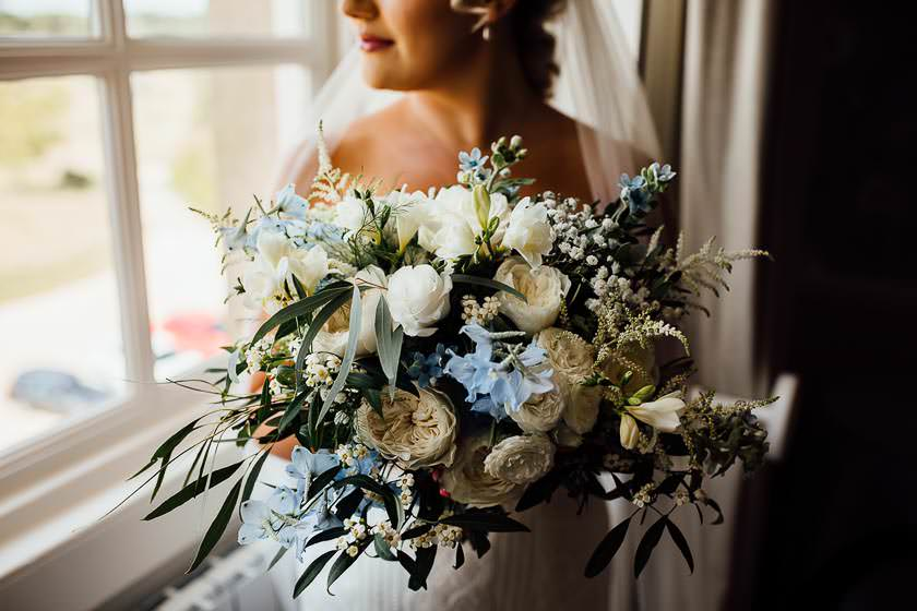 the bride is presenting her wedding bouquet created with delicate spray roses, delphinium and freesias,