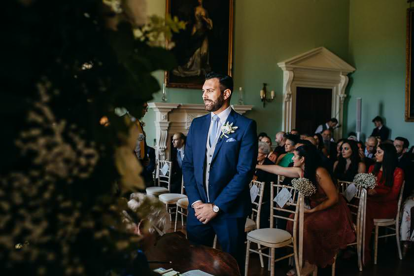 the groom is waiting in the ceremony room for the bride to arrive for the ceremony at Kirtlington Park