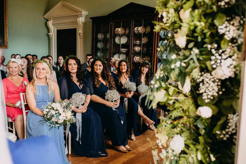 the bridesmaids are sitting on the chairs during the wedding ceremony looking at the bride and groom with the smile
