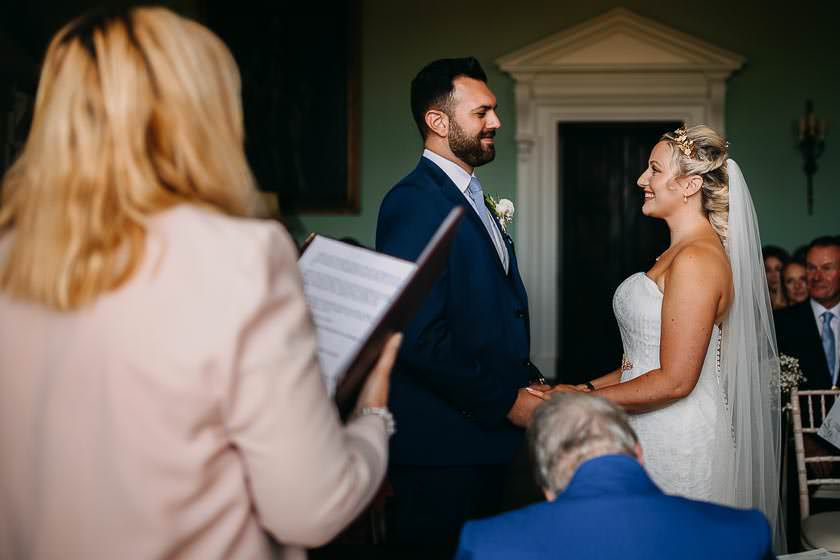 bride and groom are standing in the wedding ceremony room holding their hands and smiling to each other