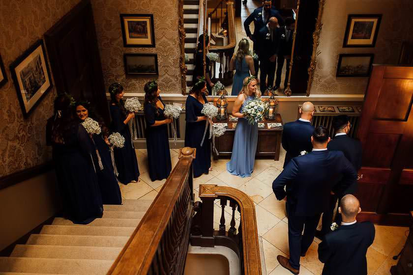 Bridesmaids and best man are standing in the hall and waiting to walk down the isle