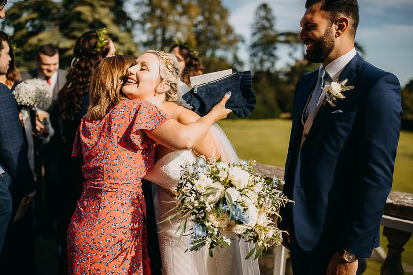 the bride is hugging with her friend outside of the Kirtlington Park wedding wenue