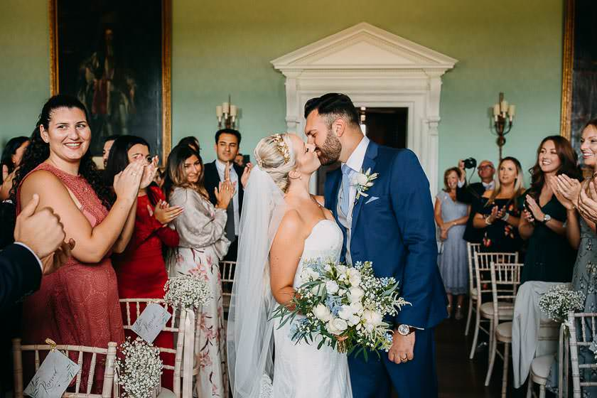 the bride and groom are kissing after the wedding ceremony at the Kirtlington Park