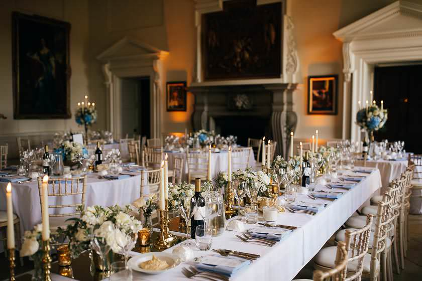 white and blue top wedding reception set up with blue table napkins and a wedding menus on the plates