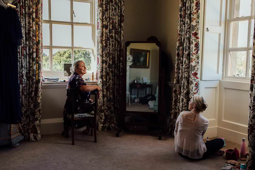 the bride is chatting to her maid of honour while she's getting ready at the Kirtlington Park