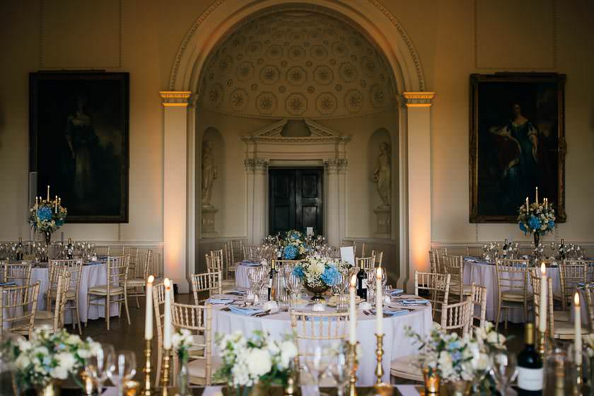 The Great Hall reception room at Kirtlington Park with a table set up and combination of tall and low flower arrangements for the reception