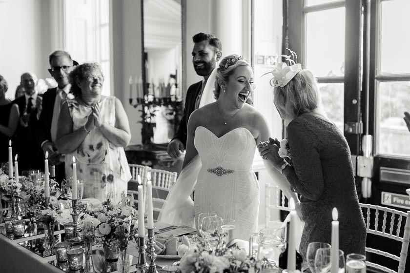 the bride is laughing with her mum just before the speeches