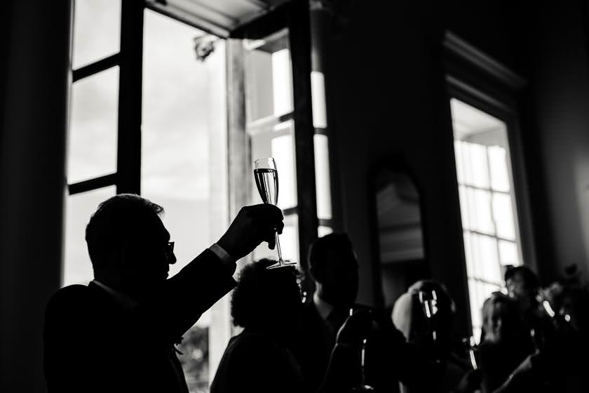 the guest is doing a toast during the wedding speeches with the sham pain glass the Kirtlington Park