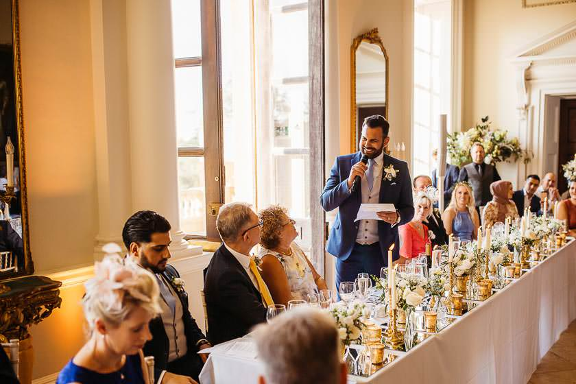 the groom is standing behind the top table bride is getting ready in the bright and sunny window light doing her eyelashes at the Kirtlington Park and he is looking at his dad during the speeches