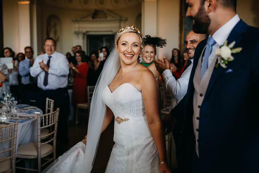 the bride walks down the dining room with a smile looking at the camera bride is getting ready in the bright and sunny window light doing her eyelashes at the Kirtlington Park