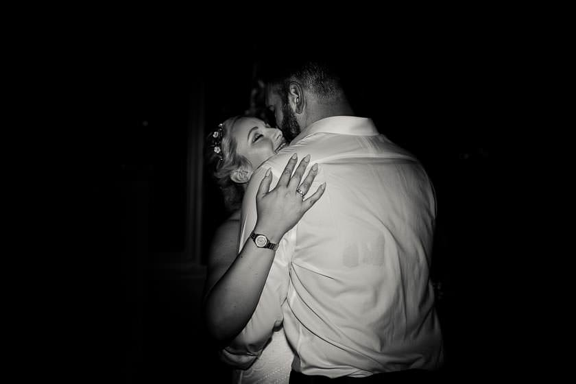 the bride and the groom are kissing on a tance floor just after the first dance