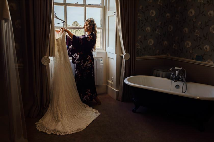 the bride is taking the wedding dress out of the hanger standing next to the window in a dressing room at the Kirtlington Park