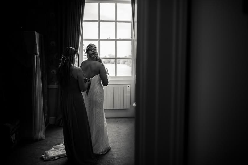 the bridesmaid is is tying a wedding dress on the bride while the bride is looking out of the window
