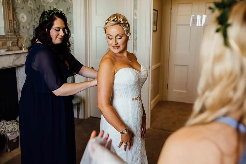 the bridesmaid is helping the bride to put the wedding dress on in the dressing room at Kirtlington Park