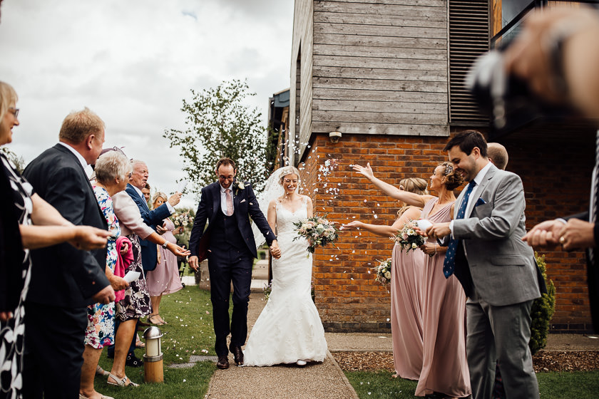 the bride and the groom are walking down the path and laughing while the wedding guest are throwing the confetti up