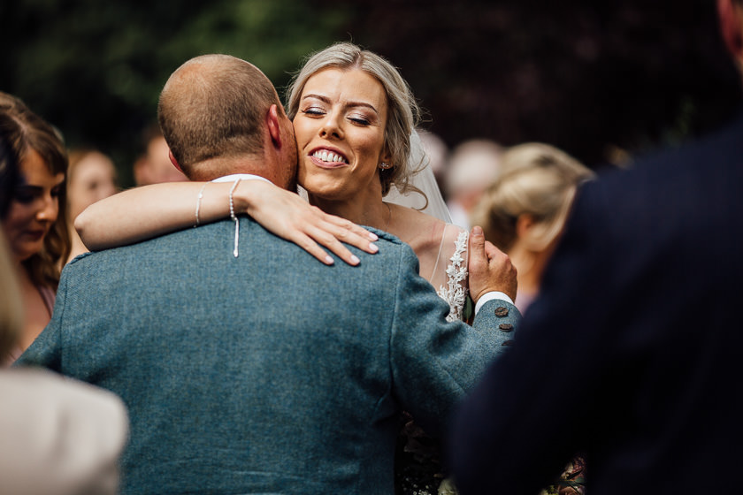 the bride is hugging and welcoming her brother at relaxed summer carriage hall wedding