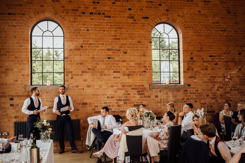 the best mans are doing the wedding speech standing infant the wedding guests relaxed and smiling in the carriage hall wedding venue hall
