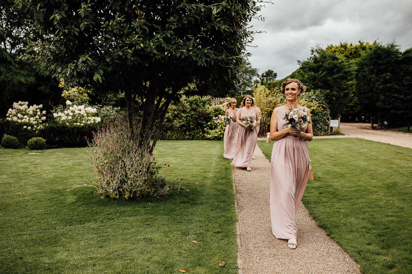 the braids maids are approaching the entrance of the carriage hall wedding wearing pink dresses and holding the flowers