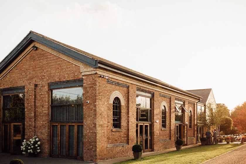 the view of the carriage hall wedding venue in the warm sunset light