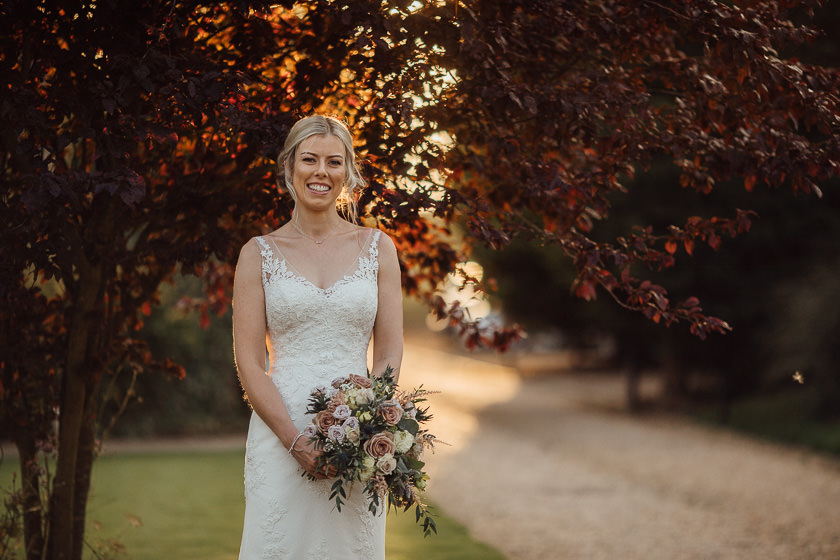 the bride is standing outside the carriage hall wedding venue holding the wedding bouquet and smiling to the camera
