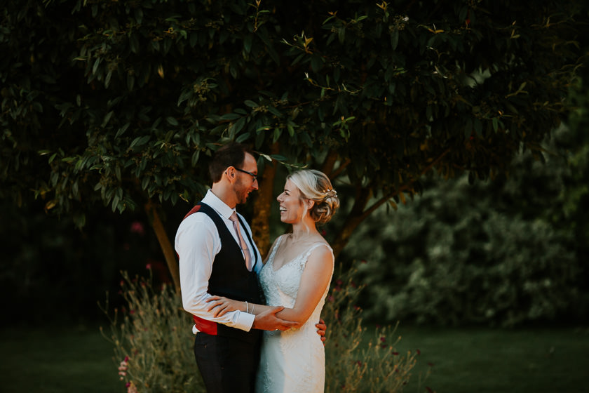 a wedding portrait of the bride and groom standing outside the carriage hall wedding venue in the evening light looking at each other