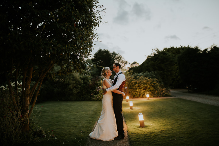 the bride and the groom are standing outside the carriage hall wedding venue in the evening light hugging and looking at each other
