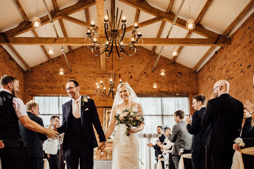 the bride and the groom are waling down the aisle after relaxed and fun wedding ceremony the carriage hall wedding venue