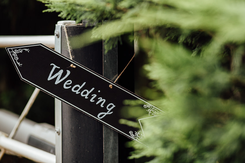 the carriage hall wedding decoration sign hanging on the venue gate showing direction to the wedding reception