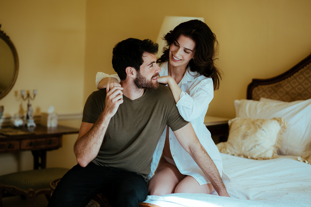 the-wedding-couple-is-seatig-on-the-bed-and-being-photographed-by-came-house-wedding-photographer